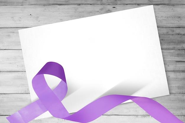 Paarse linten met blanco wit papier op houten achtergrond. wereldkankerdag concept. blanco wit papier voor kopie ruimte