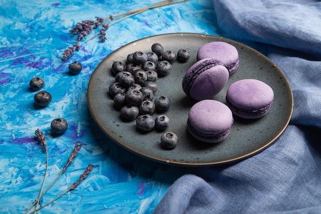 Paarse macarons of bitterkoekjes taarten met bosbessen op keramische plaat op een blauwe betonnen ondergrond en blauw textiel