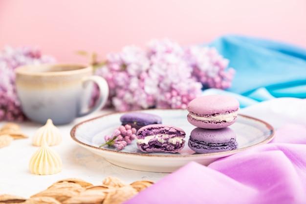 Paarse macarons of bitterkoekjes taarten met kop koffie op een witte betonnen achtergrond. zijaanzicht, selectieve aandacht.