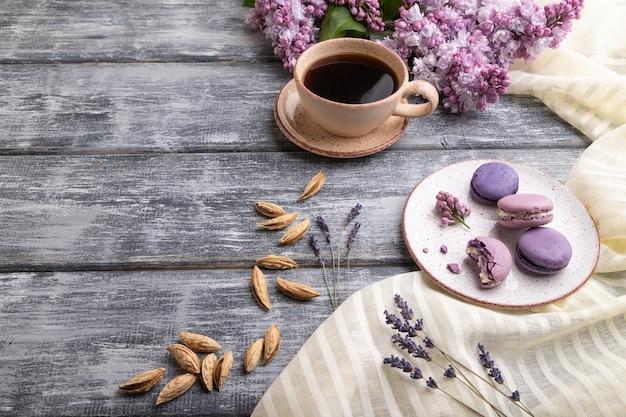 Paarse macarons of bitterkoekjes taarten met kopje koffie op een grijze houten achtergrond en wit linnen textiel. zijaanzicht,
