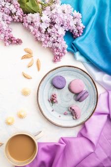 Paarse macarons of bitterkoekjes taarten met kopje koffie op een witte betonnen achtergrond en magentablue textiel. bovenaanzicht, platliggend,