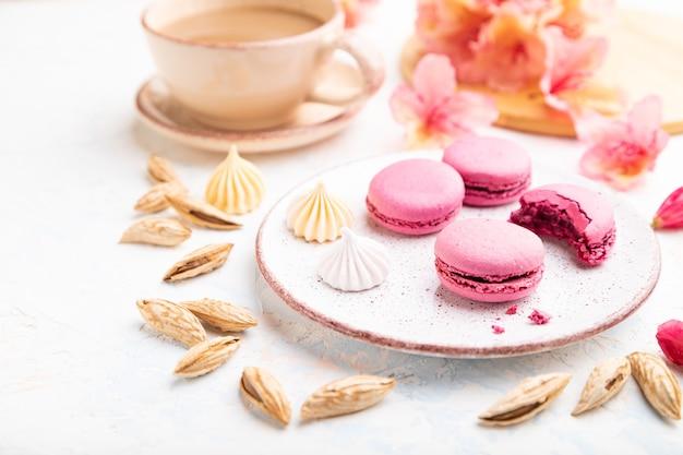 Paarse macarons of bitterkoekjes taarten met kopje koffie op een witte betonnen achtergrond versierd met bloemen. zijaanzicht,