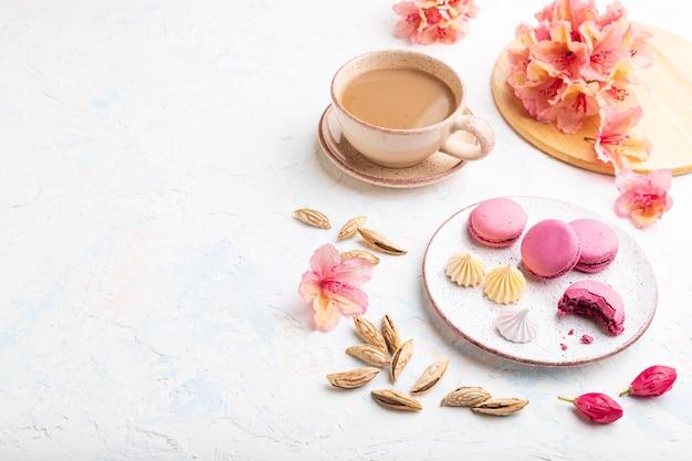 Paarse macarons of bitterkoekjes taarten met kopje koffie op een witte betonnen achtergrond versierd met bloemen.