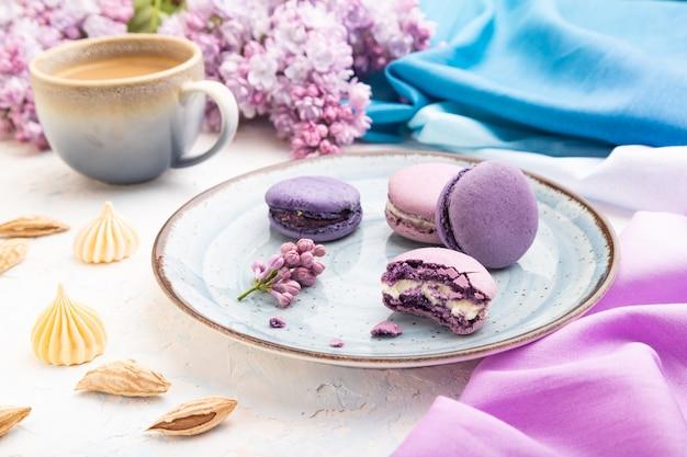 Paarse macarons of bitterkoekjes taarten met kopje koffie op een witte betonnen ondergrond en magenta-blauw textiel