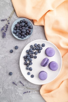 Paarse macarons of macarons cakes met bosbessen op witte keramische plaat op een grijze betonnen ondergrond en oranje textiel Premium Foto