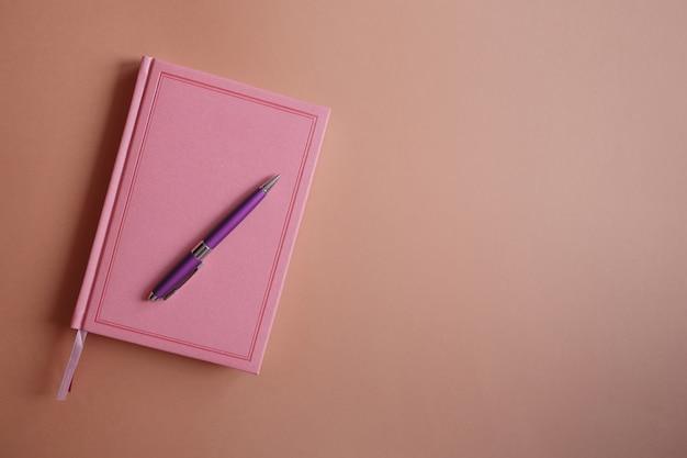Paarse metalen pen op een roze notitieboekje of dagboek, op een roze papieren achtergrond plat leggen