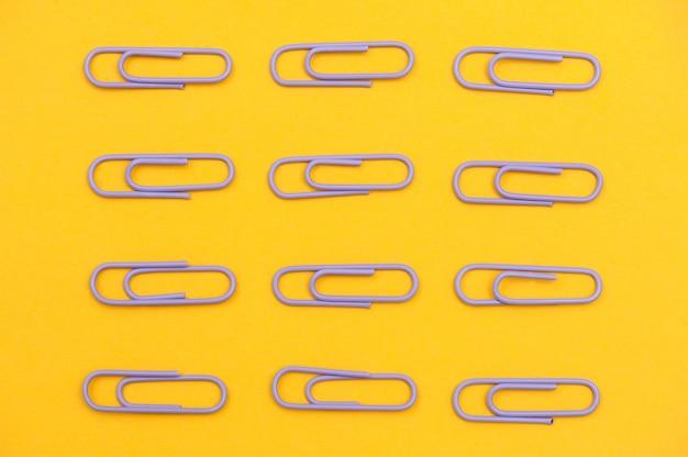 Paarse paperclips op gele achtergrond plat gelegd