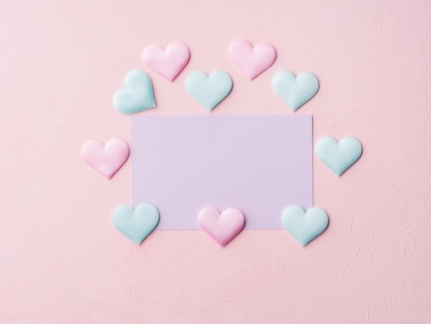 Paarse pastel kaart en harten op roze textuur
