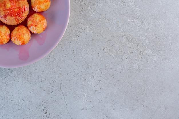 Paarse plaat van minicakes met aardbeiensaus op steen.