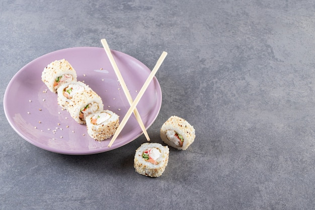 Paarse plaat van sushi rolt met sesamzaadjes op stenen achtergrond.