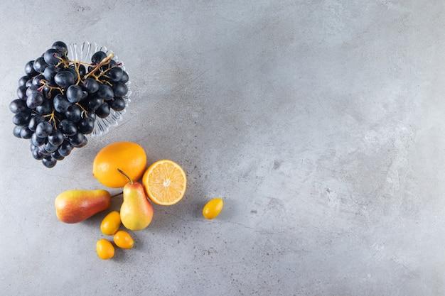 Paarse plaat van verse zwarte druiven en peren op stenen achtergrond.