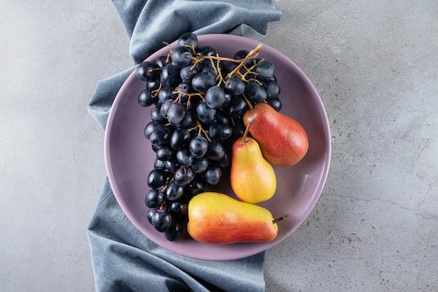 Paarse plaat van zwarte druiven en smakelijke peren op stenen achtergrond.