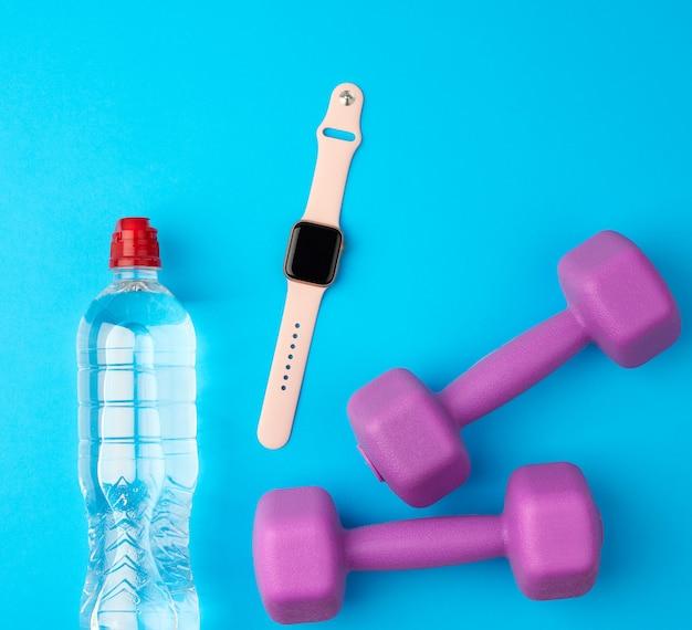 Paarse plastic kettlebells, een doorzichtige fles water en een smartwatch