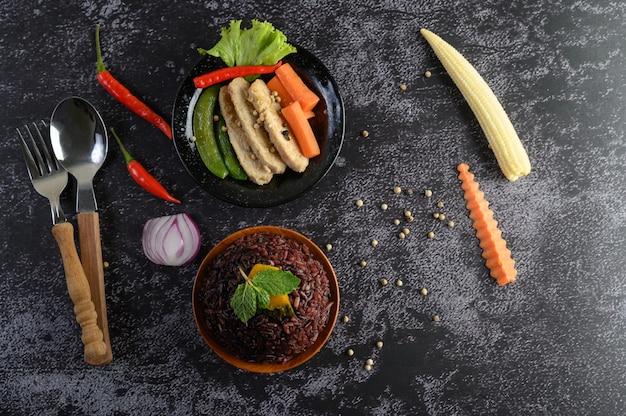 Paarse rijstbessen gekookt met gegrilde kipfilet. pompoen, wortelen en muntblaadjes in een schaaltje, schoon voedsel.
