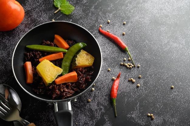 Paarse rijstbessen met erwten pompoenbladeren, wortelen en muntblaadjes in een koekenpan