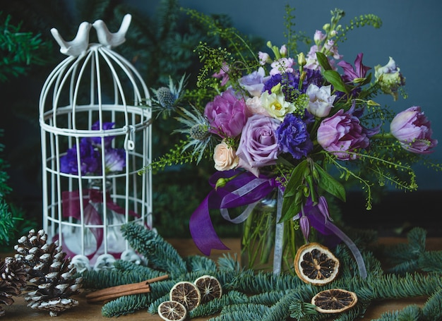 Paarse tinten gekleurd bloemboeket met kerstversiering.