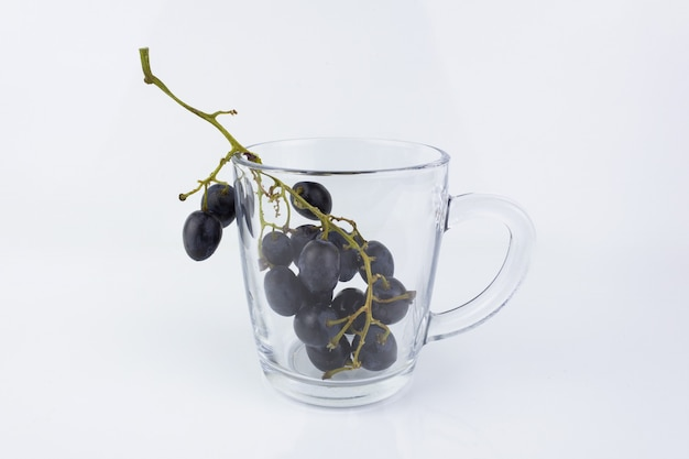 Paarse tros druiven in transparante glazen mok op witte achtergrond.