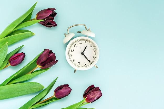 Paarse tulpen en een wekker op een blauwe achtergrond. bovenaanzicht en ruimte voor tekst