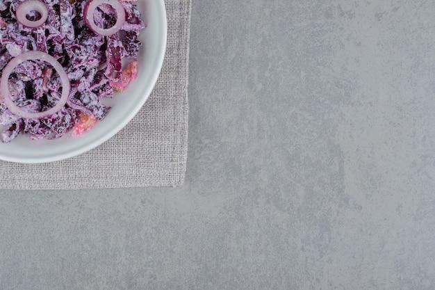 Paarse uiensalade in een wit keramisch bord