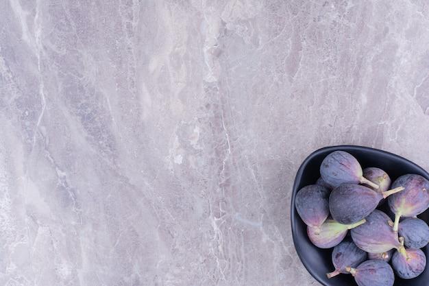 Paarse vijgen in een zwarte kom op het marmer