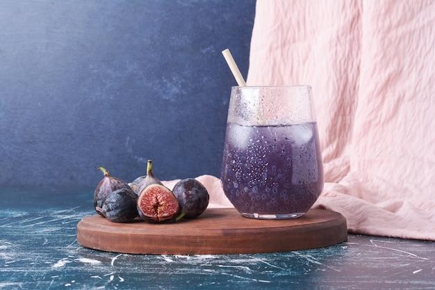 Paarse vijgen met een glas sap op blauw.