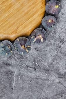 Paarse vijgen rond een houten plaat op marmer.