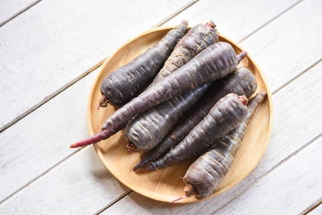 Paarse wortel op houten plaat, verse wortel voor vegetarisch koken op houten tafel