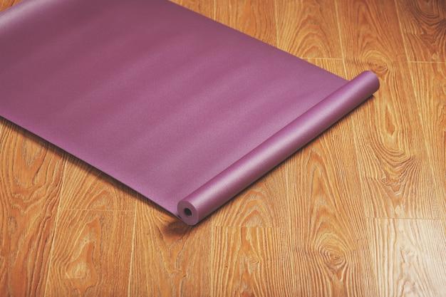 Paarse yoga- en fitnessmat op houten vloer.