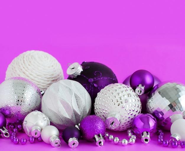 Paarse, zilveren en witte kerstballen op een paarse achtergrond