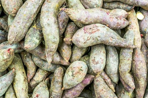 Paarse zoete aardappel op elkaar gestapeld in een markt