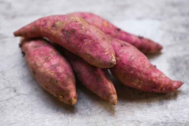 Paarse zoete aardappel op houten tafel, yam paars
