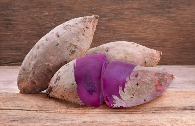Paarse zoete aardappelen op een houten tafel