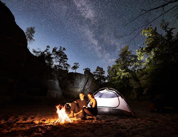 Paartoeristen die naast kamp, kampvuurtent bij nacht rusten