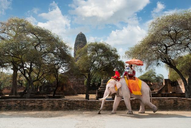 Paartoeristen die olifantsrit berijden rond de historische plaats van ayutthaya, thailand.