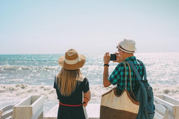 Paarvrouw en man die en foto bekijken bij stormachtige overzees