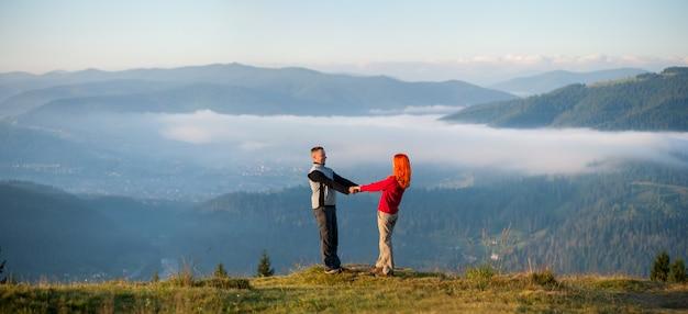 Paarwandelaars die handen houden en elkaar op een heuvel onder ogen zien