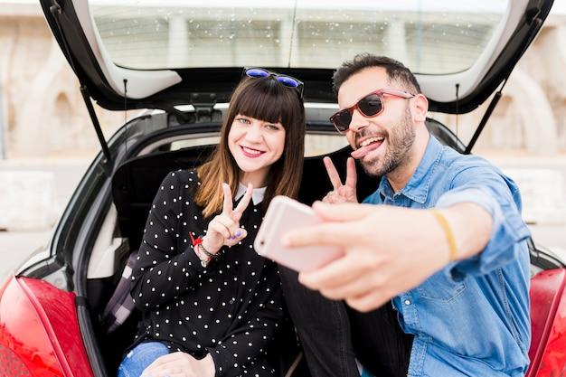 Paarzitting in autoboomstam het gesturing terwijl het nemen van zelfportret