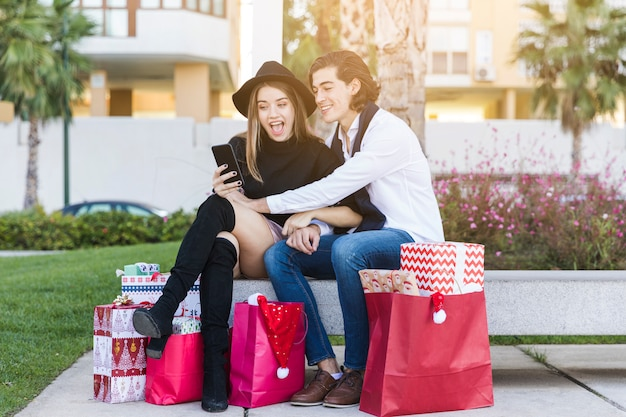 Paarzitting met smartphone op bank