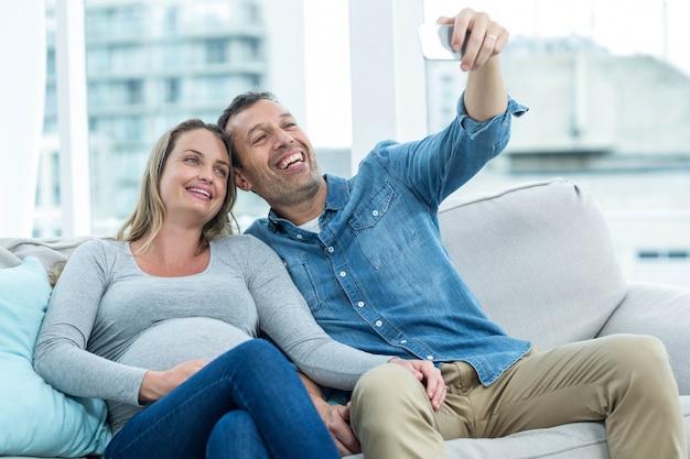 Paarzitting op bank en het nemen van een selfie op smartphone