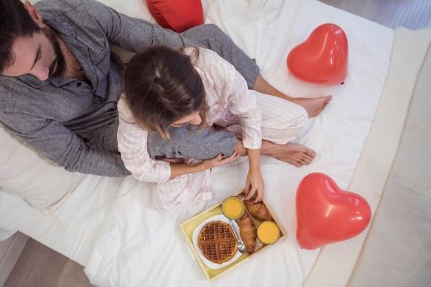 Paarzitting op bed met voedsel op dienblad
