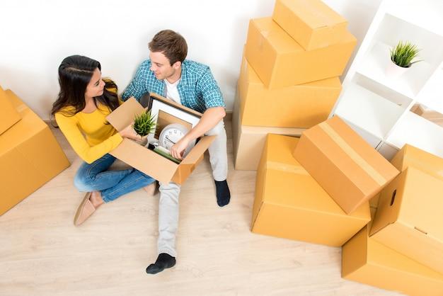 Paarzitting op de vloer uitpakkende doos na zich het bewegen in nieuw huis