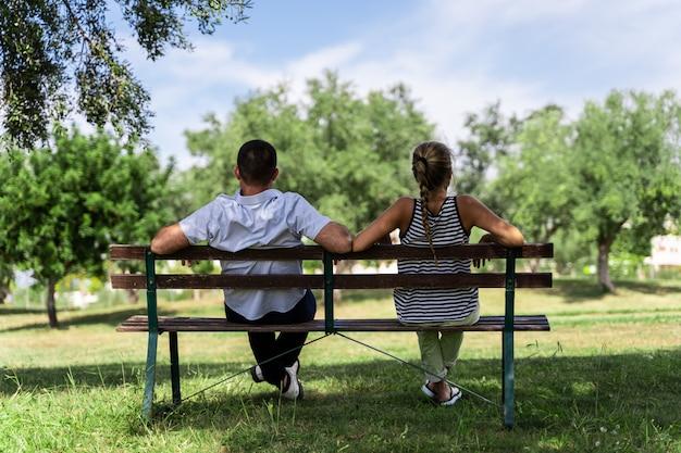 Paarzitting op een houten bank onder een boom die vooruit kijken
