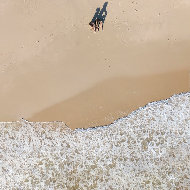 Paarzitting op kust dicht bij schuimgolven