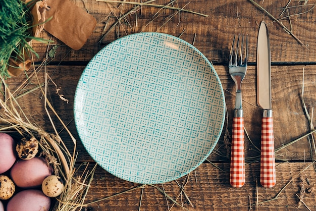 Paas diner. bovenaanzicht van paaseieren in kom en bord met vork en mes liggend op houten rustieke tafel met hooi