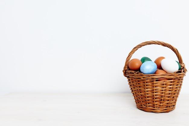 Paas eieren in een rieten mand op een lichte kopie ruimte.