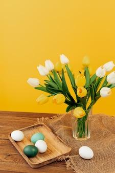 Paas eieren op een houten dienblad een boeket bloemen lente vakantie pasen gele achtergrond