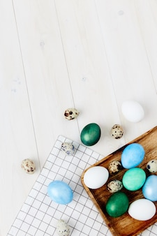 Paas eieren van verschillende kleuren liggen op een houten tafel copy space en een geruit servet