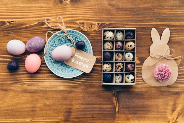 Paas vibes. bovenaanzicht van gekleurde ester-eieren op plaat en paasdecoraties liggend op houten rustieke tafel