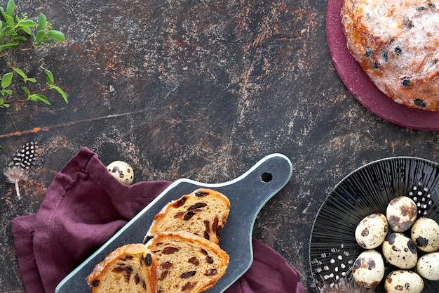Paasbrood (osterbrot in het duits). bovenaanzicht van traditionele fruitige brood op donkere tafel met verse bladeren en kwarteleitjes. kopie-ruimte.