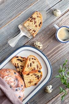 Paasbrood (osterbrot in het duits). hoogste mening van traditioneel fruitig brood op rustiek hout met verse bladeren en kwartelseieren